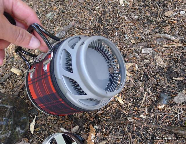 The Jetboil MiniMo backpacking stove has heat retention fins on the bottom which improve stove efficiency while helping acting as a wind screen.