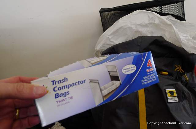 White plastic bags are inexpensive and waterproof backpack liners.